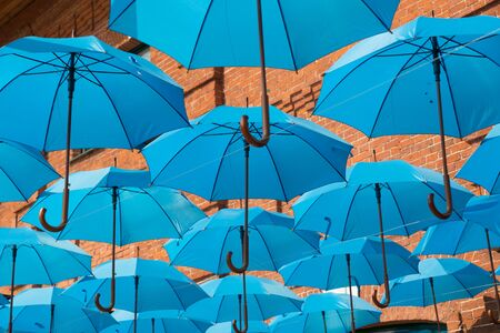 Many blue umbrellas hanging over the heads of passers-by. Standard-Bild - 139712487