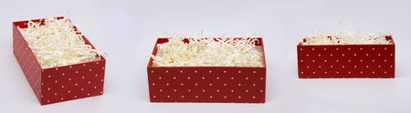 Three angles of a paper-filled red gift box isolated Standard-Bild - 140205718