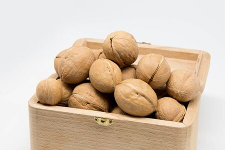 Walnuts slide in a wooden box isolated on white background. Standard-Bild - 140276070