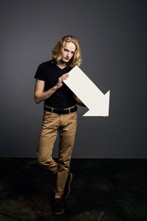 Young attractive guy with long blonde hair holds a large white arrow pointing down with a dejected face on a gray