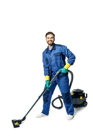 Young handsome man with a beard in a blue working uniform for cleaning rooms smiling and vacuuming isolated on white background.