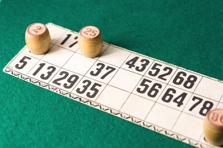 Old wooden lotto barrels and playing cards isolated on white