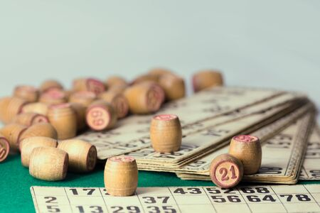 Old wooden lotto barrels and playing cards isolated