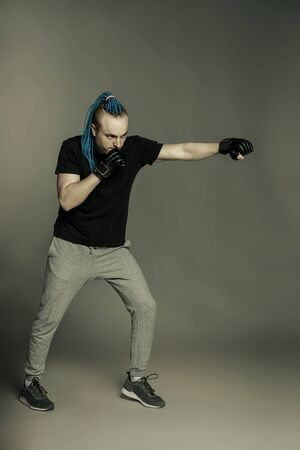 A man with an unusual hairstyle of mohawk from blue braids in boxing gloves poses and is ready for battle on a dark background