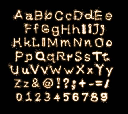 English alphabet written on a black background sparkler, numbers and signs. 스톡 콘텐츠