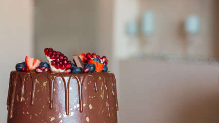 Appetizing chocolate cake decorated with strawberries, blueberries and a pomegranate on an orange background.