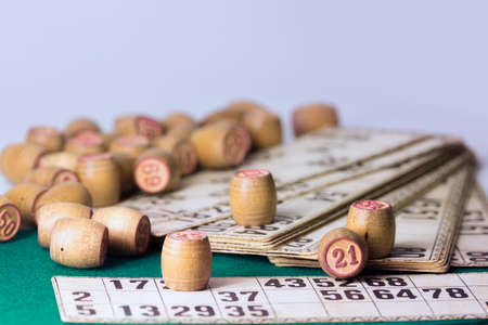Old wooden lotto barrels and playing cards isolated on light background.