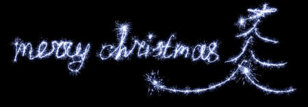 Merry christmas lettering with sparklers on black background.