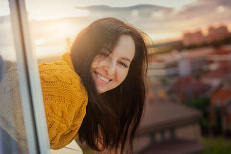 A young beautiful girl in a yellow sweater looks out of the window on the eighth floor against the backdrop of the sunset and smiles