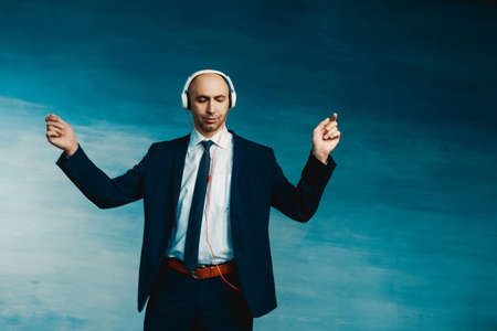 A bald man in blue formal suit and tie dancing in headphones on a blue background.