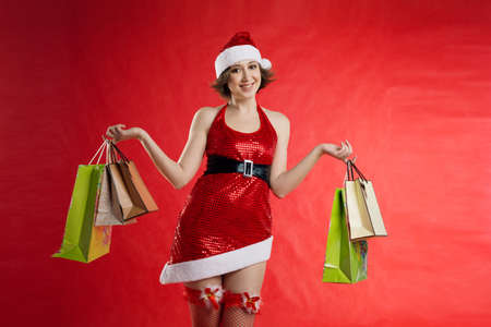 A young woman elf dressed as Santa in round glasses holds d background, hands holding a gift package, many paper bags from the store.