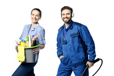 Young bearded handsome guy and a girl in a uniform of cleaners are isolated on a white background. In the hands of a bucket with cleaning products and rags and a vacuum cleaner.