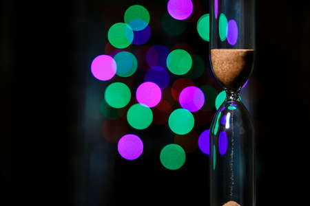 Hourglass in the right. Sand strews down on christmas background, bokeh blue, green, violet christmas lights. Time flow.