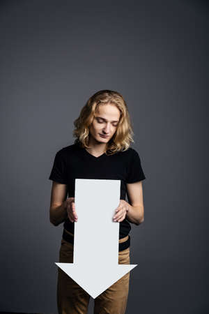 Young attractive guy with long blonde hair holds a large white arrow pointing down with a dejected face on a gray background