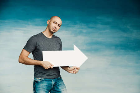 A tall bald man in a gray T shirt and blue jeans holds a pointer in the form of an arrow pointing to the side