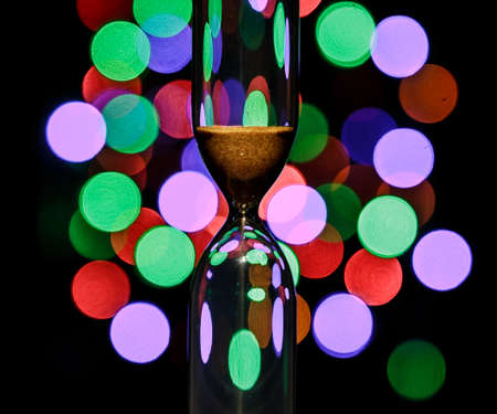 Hourglass in the center. Sand strews down on christmas background, bokeh multi-colored christmas lights.