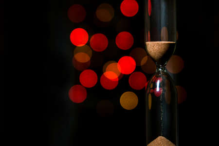 Hourglass in the center. Sand strews down on christmas background, bokeh red christmas lights.