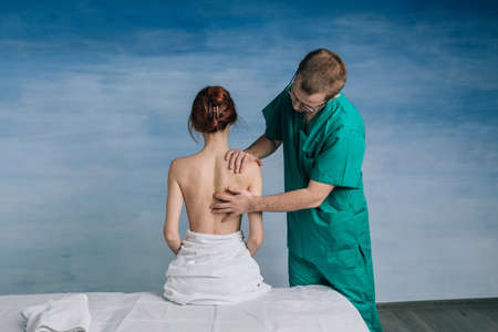 The male doctor n glasses and a green uniform examines the patient.