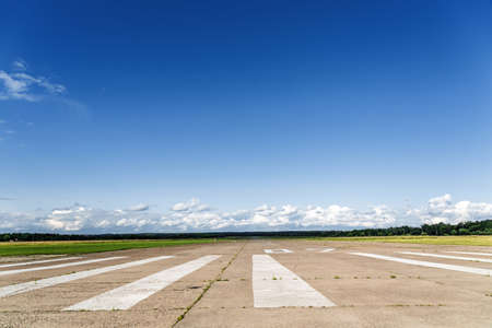 The runway of a rural small airfield against a blue sky with clouds of the airfield.
