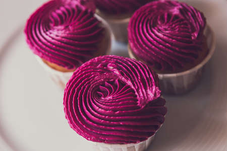 Three cupcakes with pink cream on a plate top view