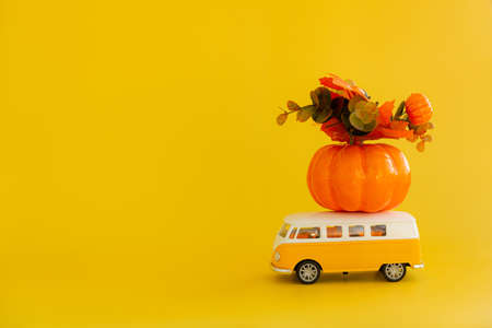 A toy minivan for a hippie carrying a pumpkin for Halloween on a yellow background.