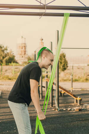 Young male trainer with mohawk hairstyle doing triceps exercise with rubber band expander on the street playground.