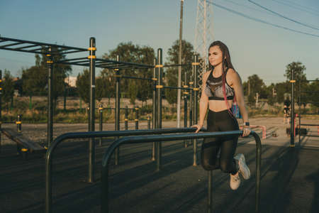 A girl of an athletic physique is engaged on the uneven bars on a street playground.