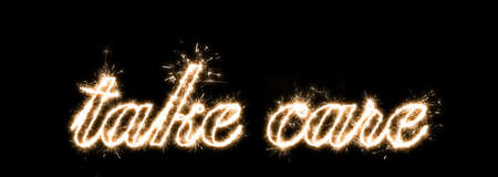 The inscription with sparklers on a black background take care.