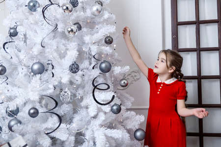 Little girl decorates the Christmas tree in red dress.