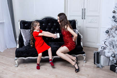 Mom and daughter in red dresses unpack New Year's gifts on the sofa.