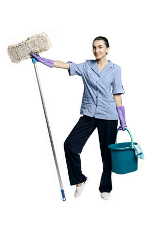 Young beautiful woman in a maid costume smiling holding a bucket and a mop, isolated on a white background.