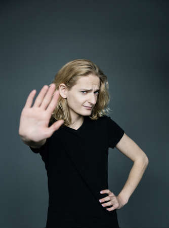 Young handsome guy with long blonde hair holds a hand in protest covering his face on a gray background.