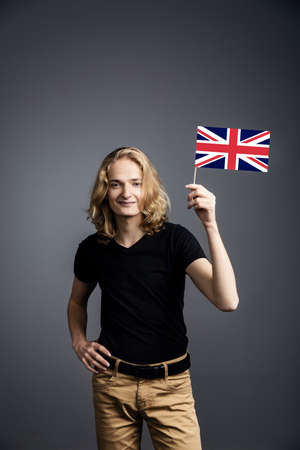 A young guy with long blonde hair in a nuclear t-shirt smiles and waves the UK flag on a gray background.