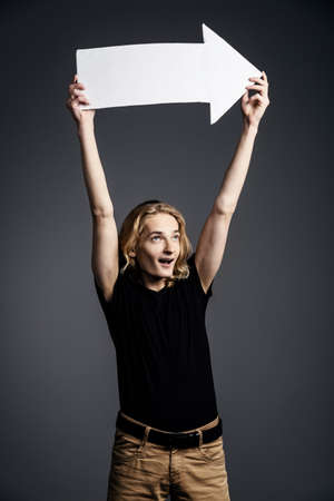 A handsome young guy with long blonde hair with wide eyes, he screams and holds on outstretched arms a white arrow directed to the right on a gray background.