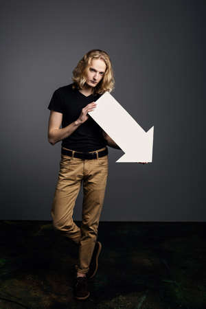 Young attractive guy with long blonde hair holds a large white arrow pointing down with a dejected face on a gray background.