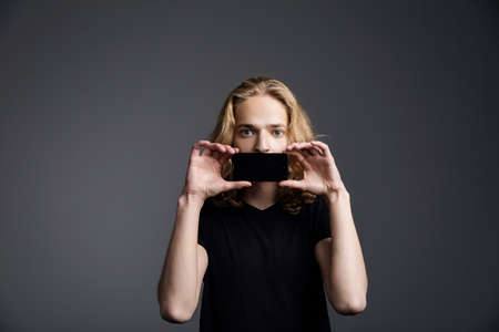 A young guy with long blonde hair closes his mouth with a phone on a gray background.