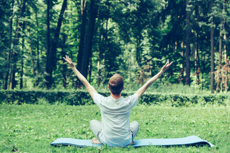 Young attractive man in sport clothes is meditating in the lotus position in the park against the background of grass and trees. Hands up to the sky.