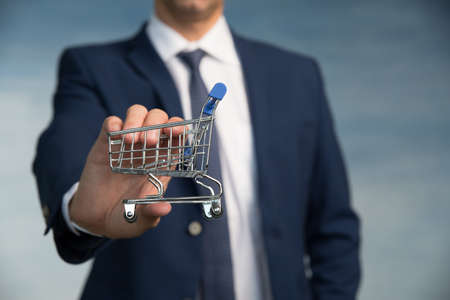 Male hand of a businessman in a blue suit with a tie hold a mini shopping trolley.