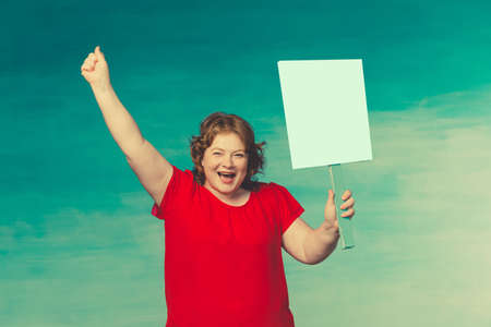 Cute smiling chubby red-haired woman screaming fervently, waving his hand in the second holds a protest poster on a blue background.