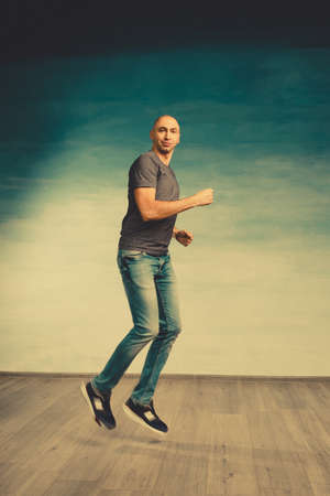 A cool bald man in jeans and a gray T-shirt runs against the background of the greenish wall.