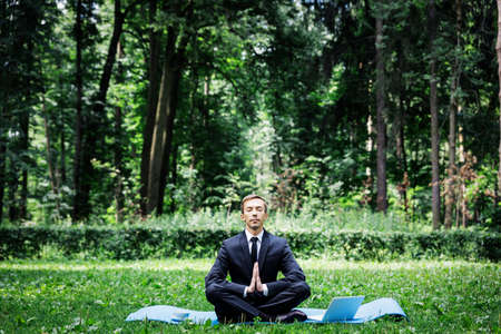 Man in a suit with tie. Business man relaxing in a park in the lotus position, he cant relax in any way, meditation in the park with a computer and a cup of coffee.
