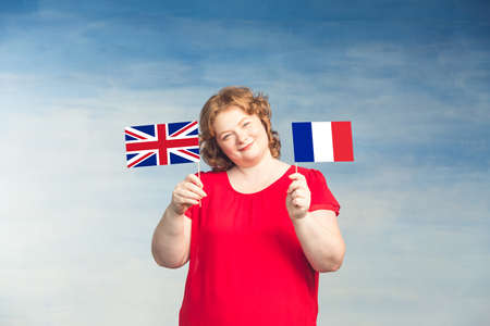 Red-haired plump woman holding French and British flags in front of him on a blue background. Stock fotó