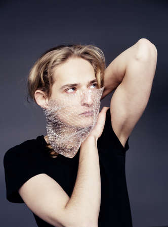 A handsome young guy with long blonde hair and sad blue eyes holds a wrap in front of his face on a gray background.