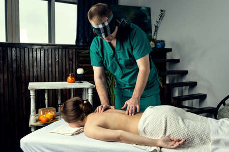 Masseur with blindfold doing blind massage of a young woman. Beautiful relaxed face of a young woman with brown hair and closed eyes.