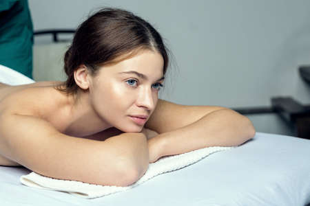 Young beautiful girl in a towel with opened eyes meditates before spa treatments. Stock fotó