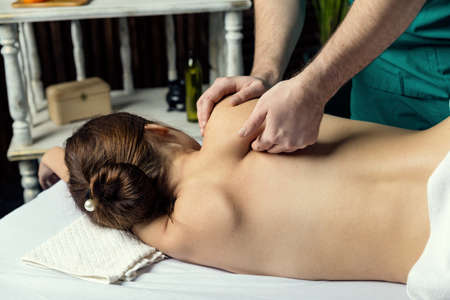 The hands of a male masseur doing massage of a young woman. Beautiful relaxed face of a young woman with brown hair. Stock fotó