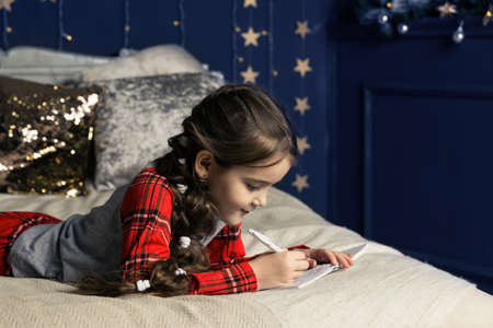A girl in pajamas lies on the bed and writes a letter to Santa Claus or grandfather frost on the background of a Christmas tree.