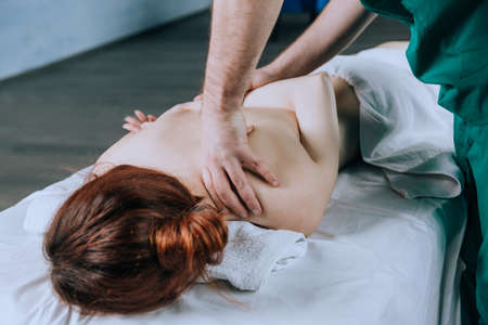 Massage therapist doing massotherapy of a young woman, elbow joint massage. Stock fotó