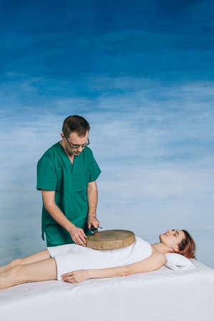 The therapy of a woman with a tambourine. Male masseur does nontraditional methods of medicine. Beautiful relaxed face of a young woman with brown hair and closed eyes.