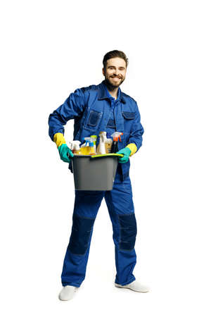 Attractive young man in cleaning uniform holding a bucket of cleaning products in his hands, isolated on white background. Stock fotó